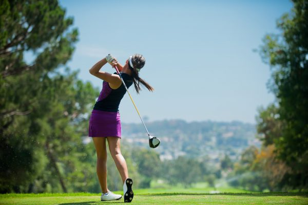 A golfer at the end of her golf swing.
